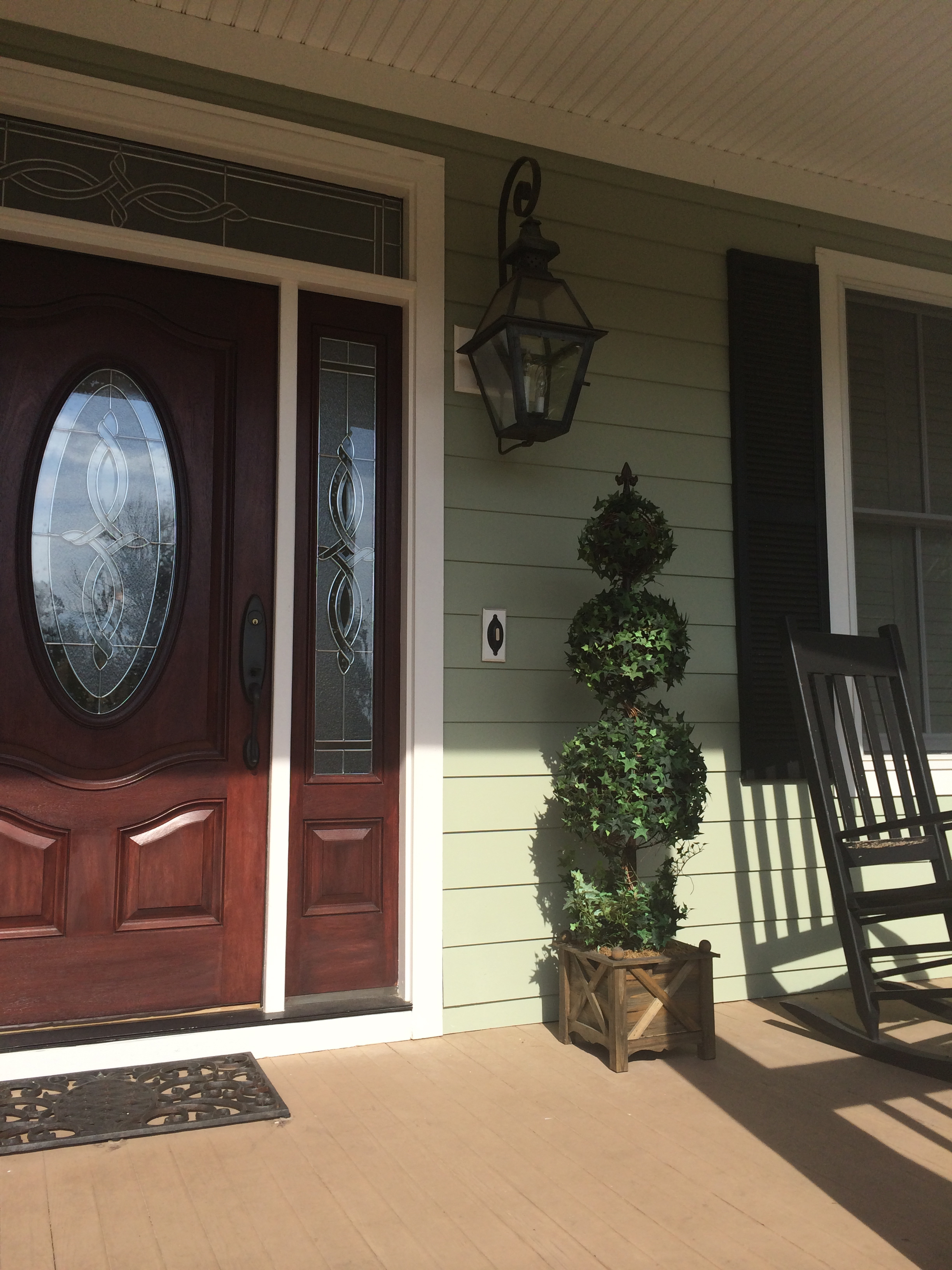 Create a welcoming entry with an artificial topiary or two for Front door not centered